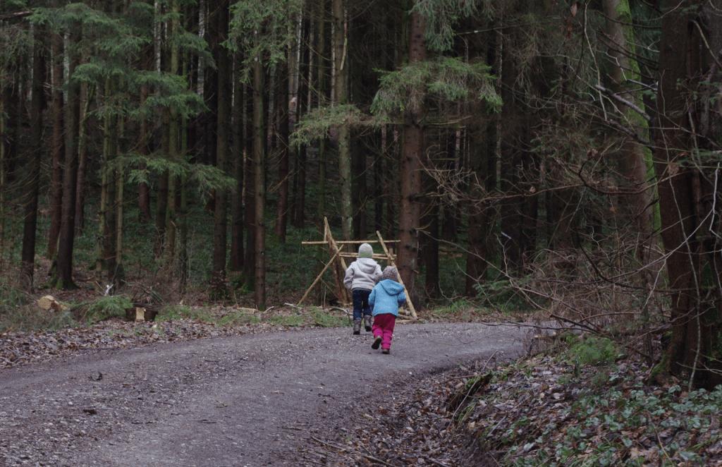 Elija und Mila rennen sofort auf dem Schotterweg in den Wald hinein.